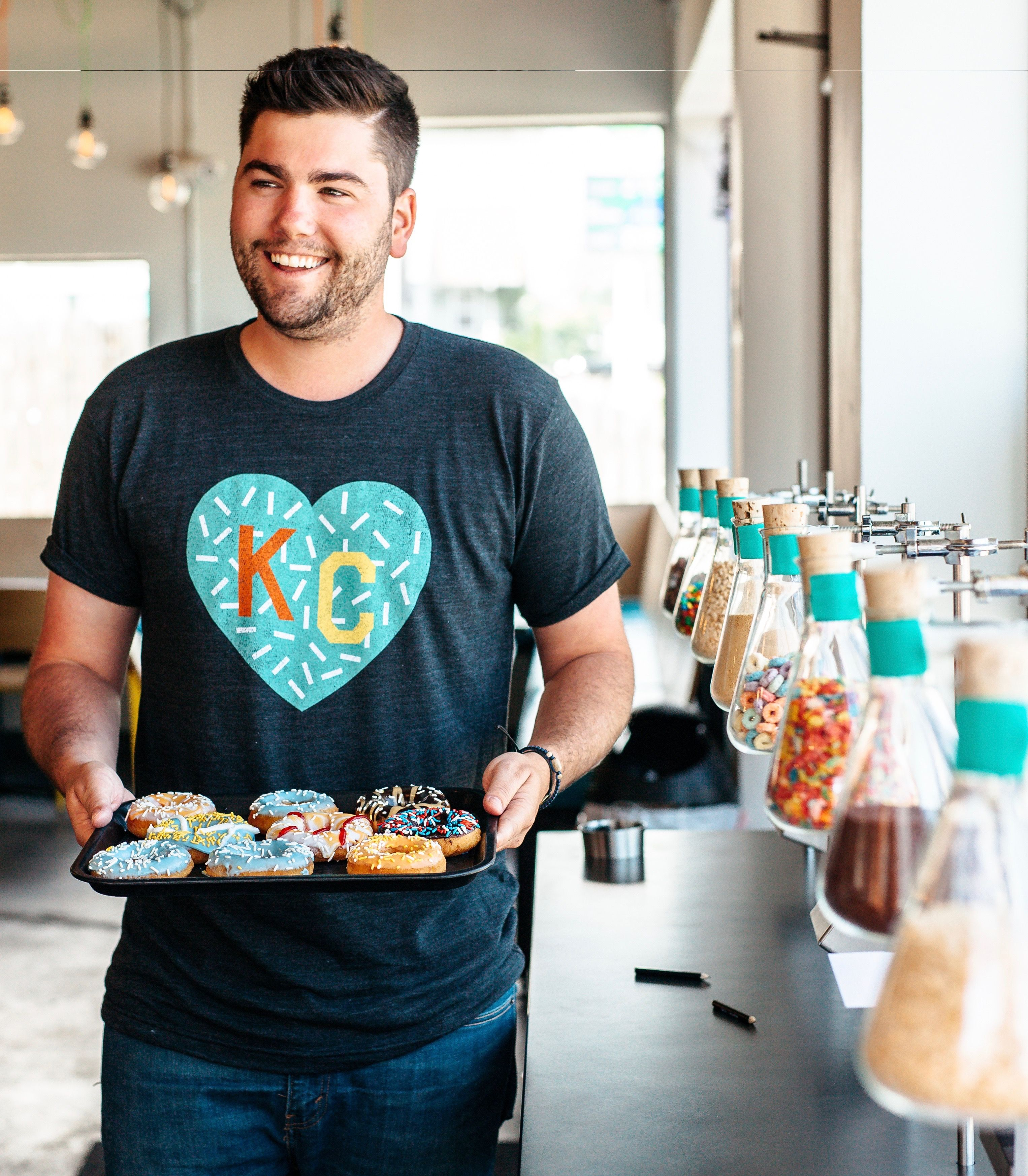 """Here at Charlie Hustle, we're celebrating National Donut Day all month long. This limited edition KC Heart tee is decked out in sprinkles and frosting and is only available for a short time. This product is part of """"The Donutology Collection"""" - Visit Donutology in Westport to see the full lineup!"""