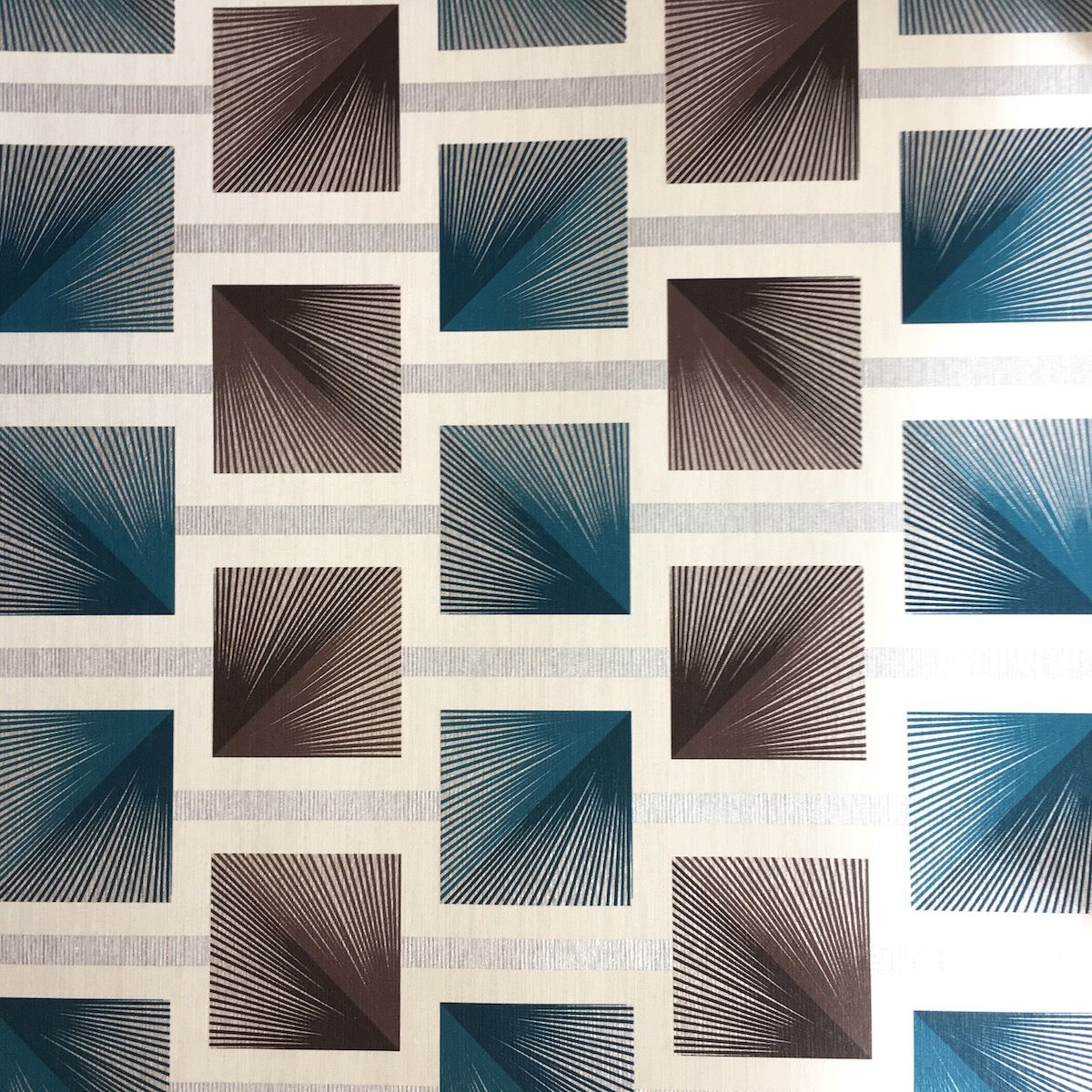 A boldsymmetrical retro square design in teal, brown and silveron a cream background and printed on a heavy weight vinyl wallpaper Co-ordinates with our Calico plain cream wallpaper