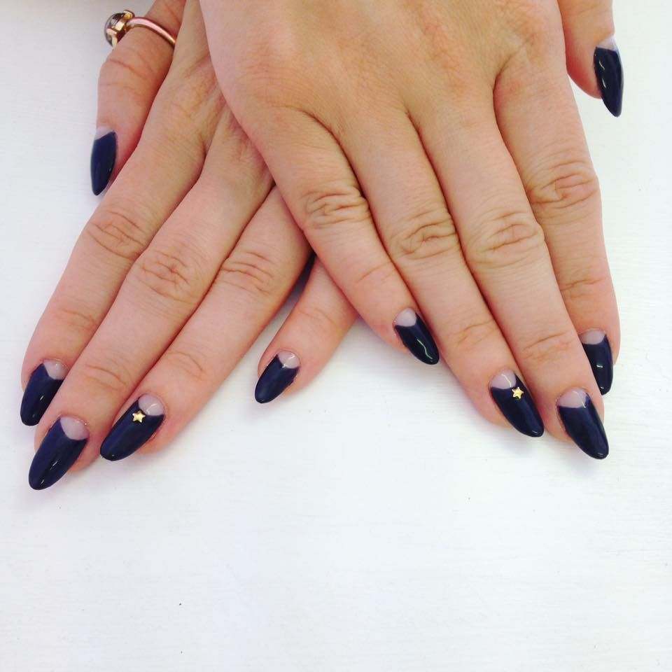 Dark Navy Oval Almond Nails With Negative E Half Moons And Small Star Details