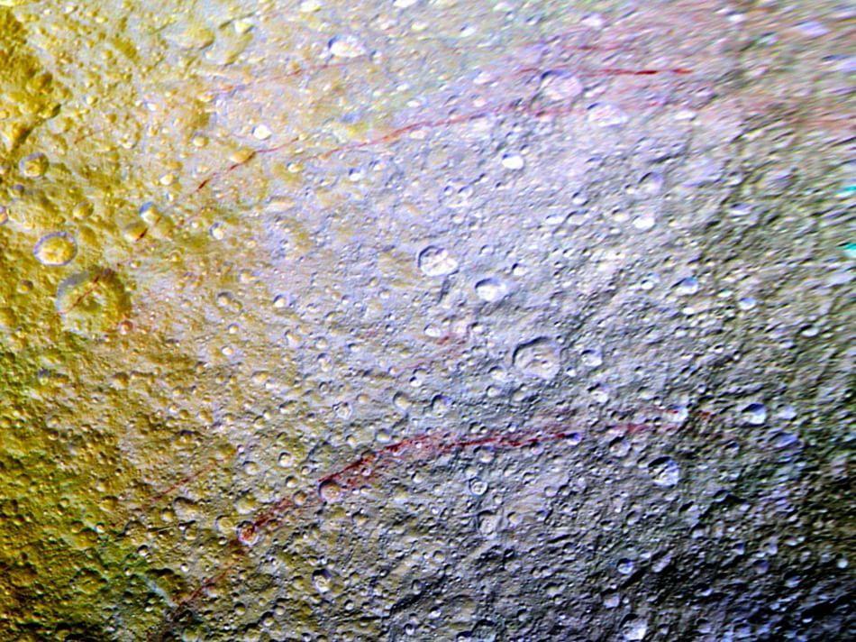 Le fotocamere della sonda Cassini hanno catturato queste misteriose linee rosse sulla superficie di Teti, una delle lune del pianeta. Gli astronomi non sanno né cosa siano né perché siano rosse queste linee lunghe centinaia di chilometri
