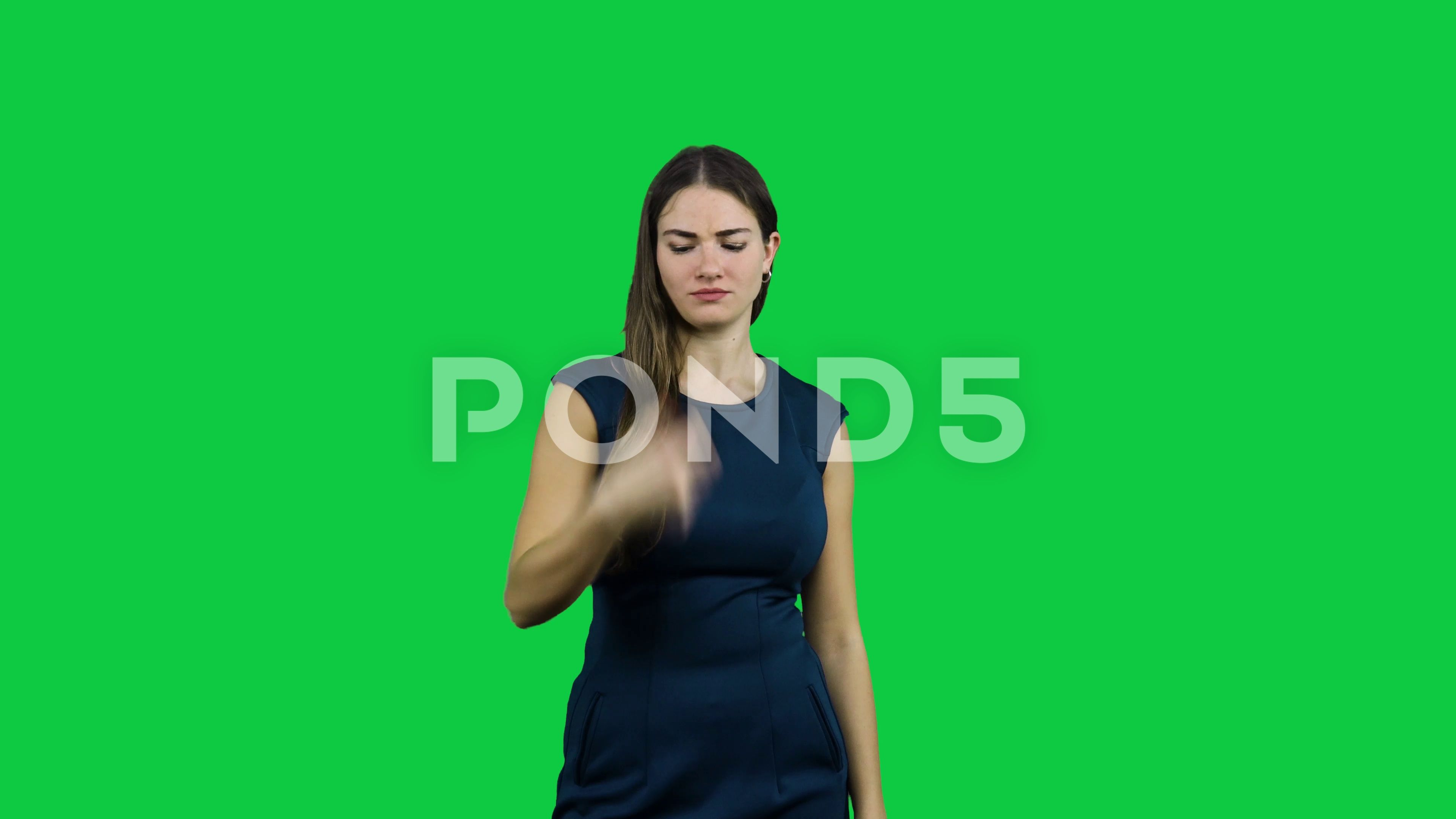 Girl usees a broken tv remote in front of a green screen