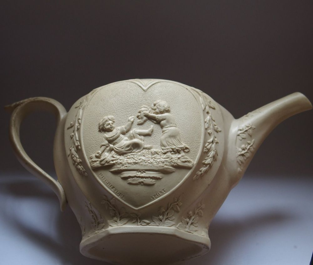 18th Century Stoneware  Mischievous Sport/Sportive Innocence  Teapot Unusual stoneware/feldspar teapot, decorated with raised heart medallions enclosing pictorial representations of word play....sportive innocence and mischievous sport. The original lid would have been decorated with a swan finial.  Dimensions - height, 11 cm, handle to spout, 22.5 cm   Condition - v good, no lid £106