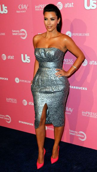 1b91b942f43 Kim Kardashian wears a strapless silver textured cocktail dress teamed with  a pair of pink heels.