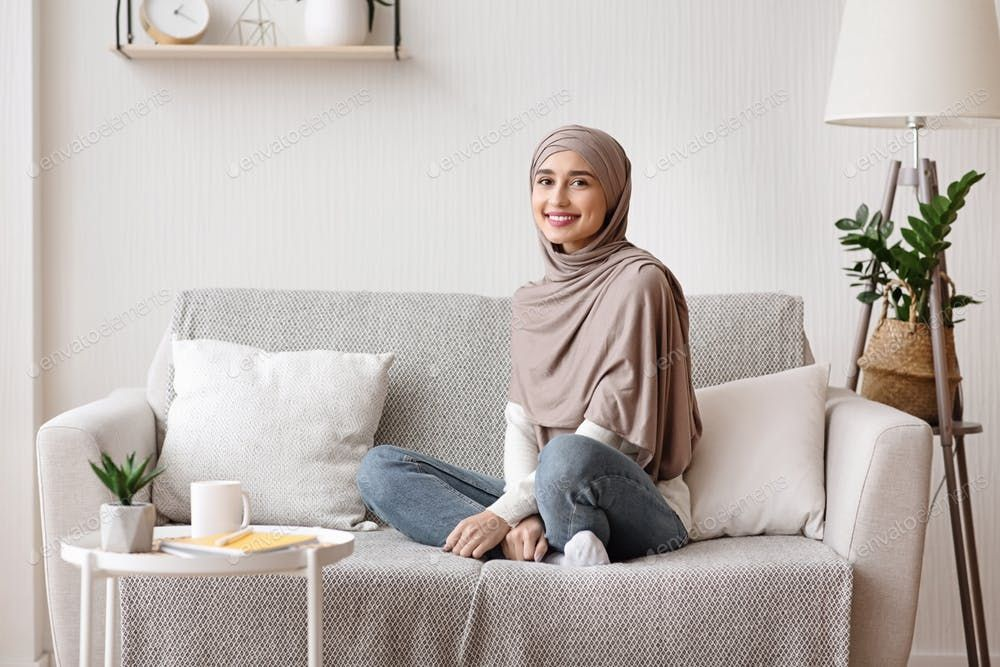 Beautiful Muslim Girl In Hijab Posing On Sofa At Home Photo By Prostock Studio On Envato Elements Muslim Girls Home Stylish Living Room