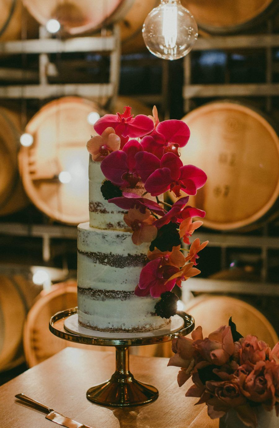 nearly naked wedding cake with pink orchids