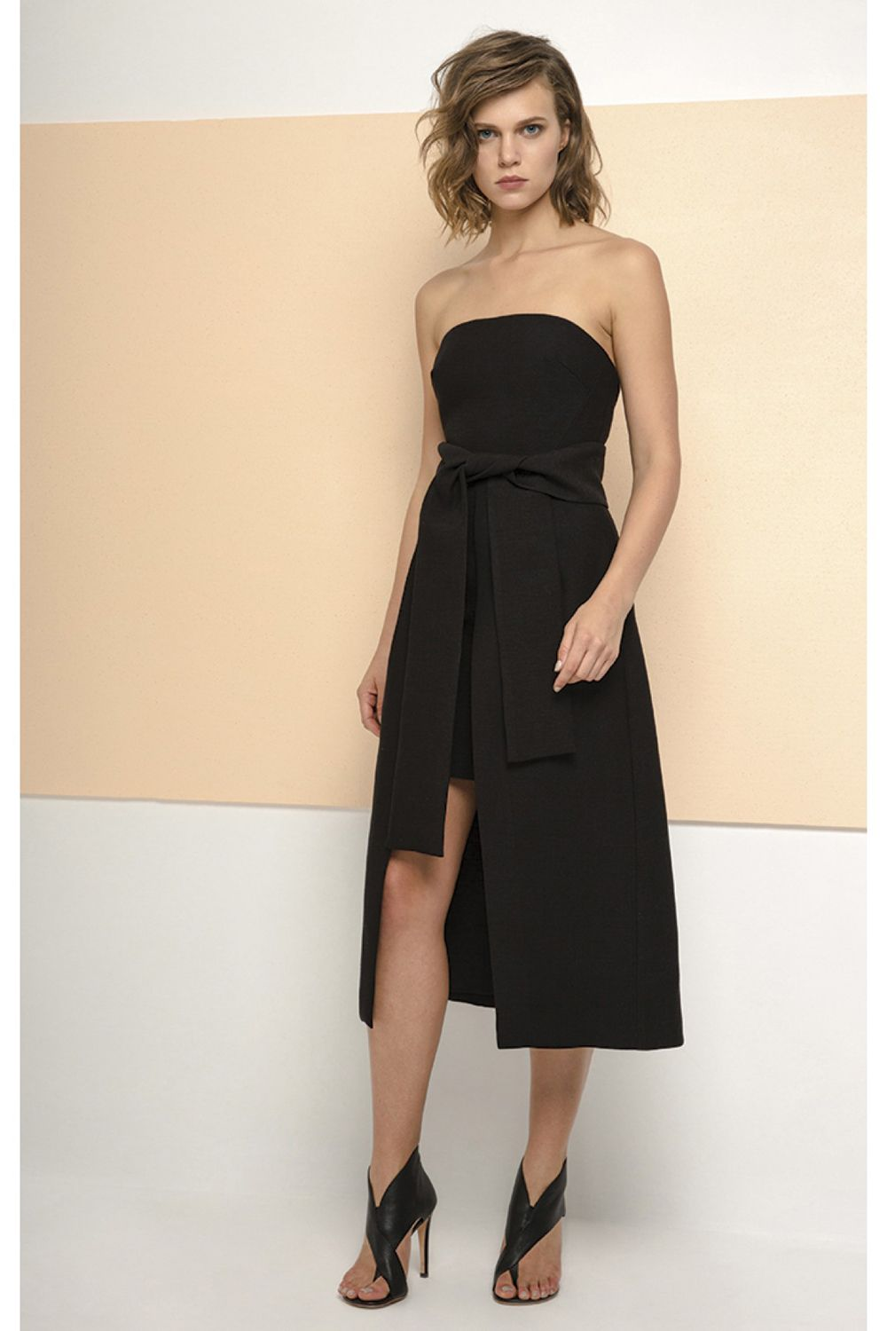 The wake me dress is a fitted strapless dress with a long open front