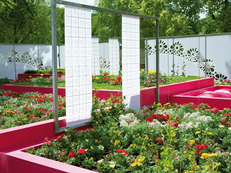 The bright pink walls of these raised flower garden beds define this ...