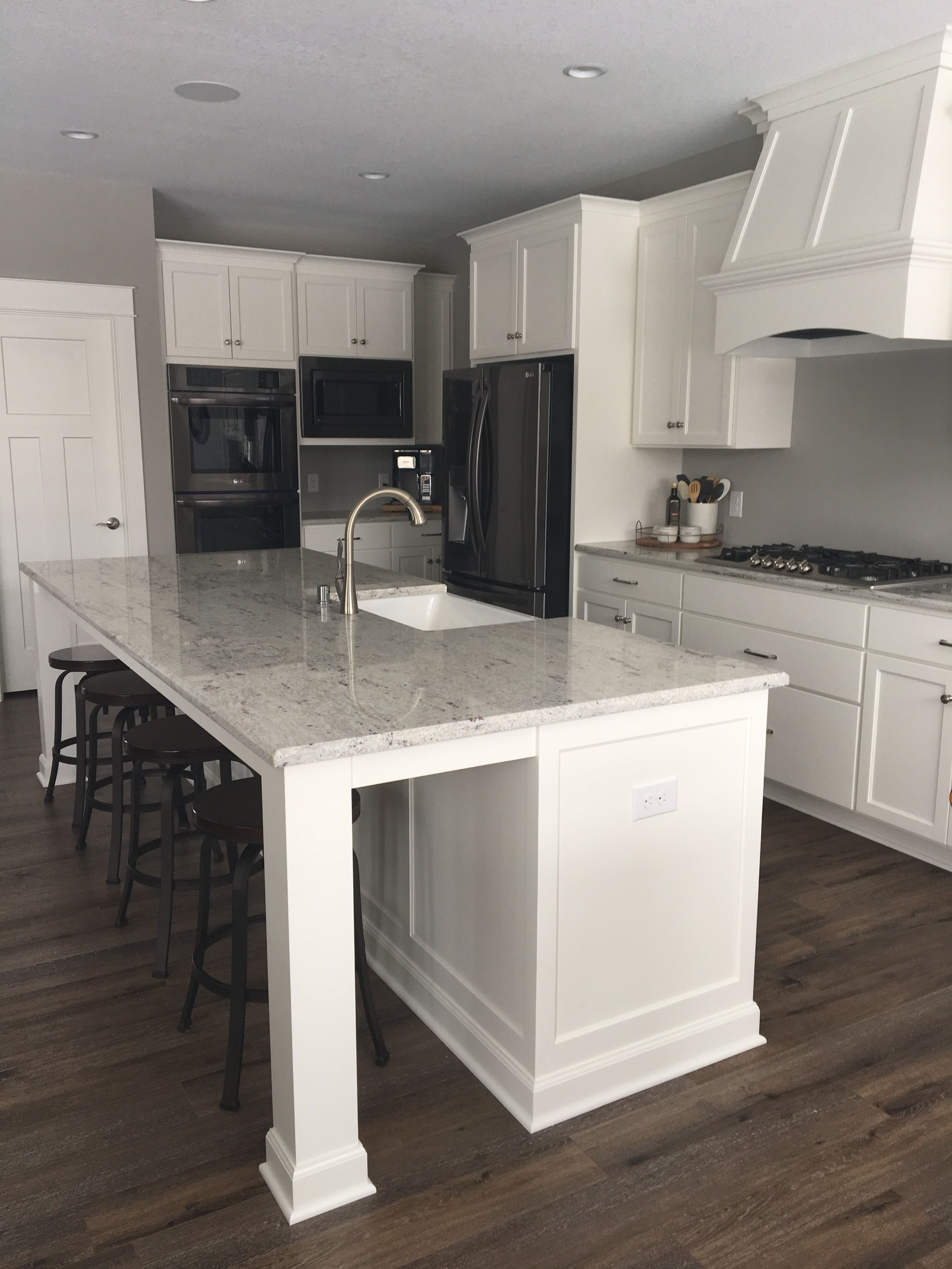This White Kitchen Is Classic Yet Modern And Features Crisp White Cabinetry An Oversized Fu Black Appliances Kitchen White Kitchen Appliances White Cabinetry