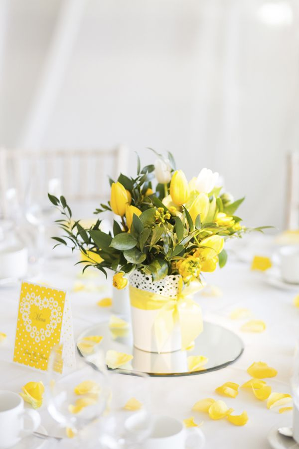 yellow themed floral decorations on a table at a wedding