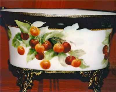 Painting of red cherries on fancy porcelain bowl with dark border by artist and china painting teacher, Jane Wright