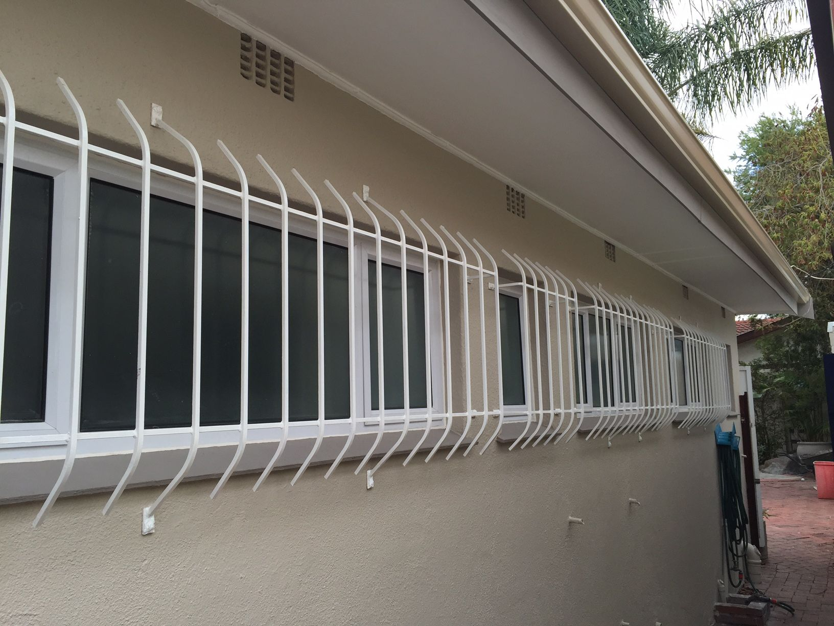 External redecoration with white burglar bars seamless gutters and
