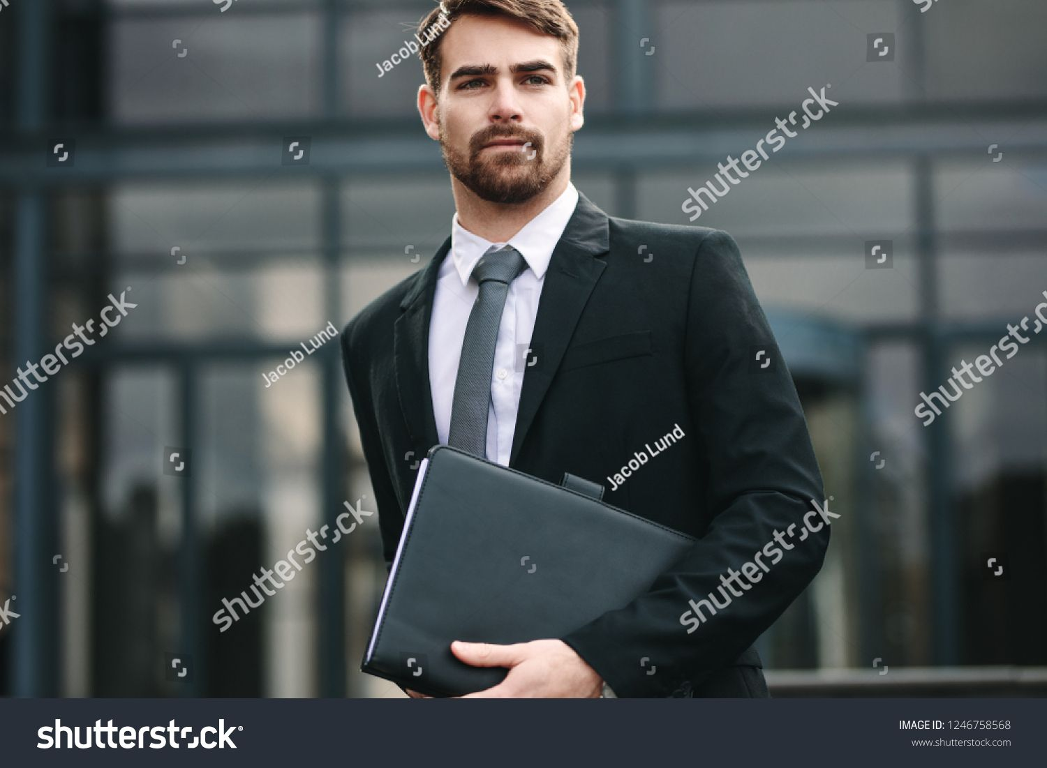 Portrait Of Handsome Businessman With A Folder Walking Outdoors