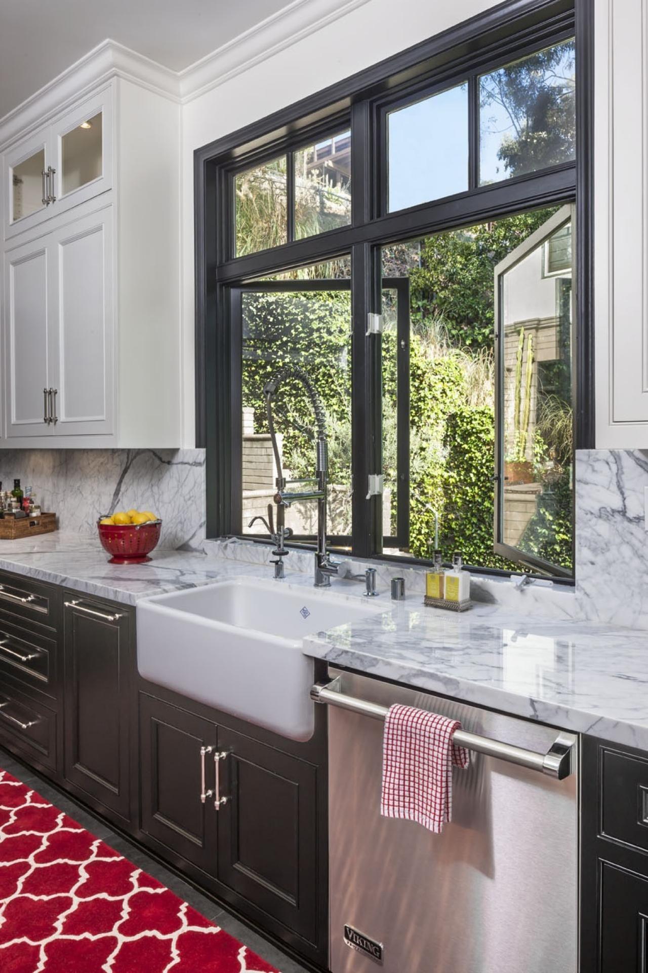 Low window behind kitchen sink  a white farmhouse sink sits below a darkframed window that opens