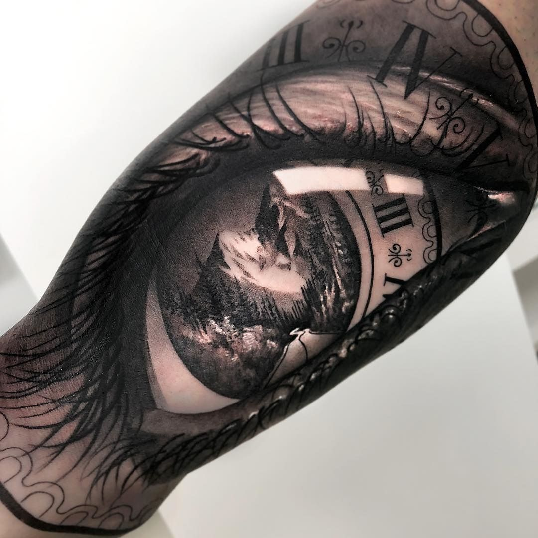 2f82d3859 B&G men's bicep tattoo with a merging of a human eye, clock face and a  mountain road scene.