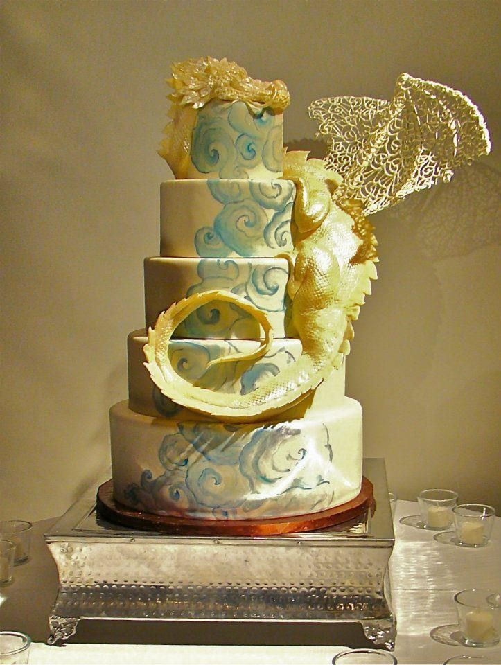 This dramatic wedding cake, topped with a dragon and a hand-painted ...