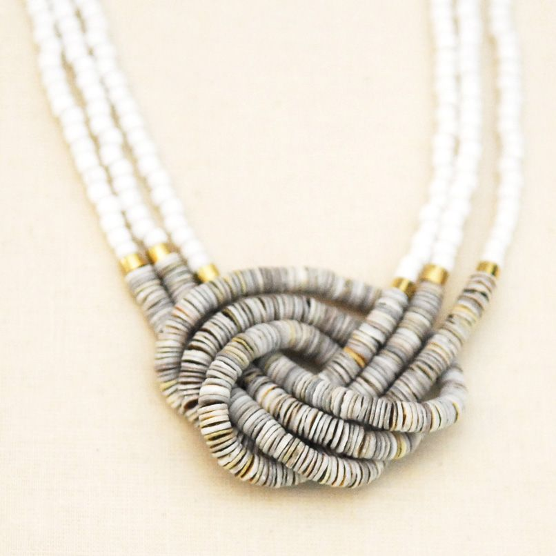 """Growing Jewelry. Overhand knot pendant necklace. Multiple strands of oyster shell beads. Brass heishi bead accents. White Japanese glass beads. Coated hemp knot at back. Slips overhead. One size. Approximately 14"""" long.  Great for layering. Shipped with logo-stamped drawstring bag."""