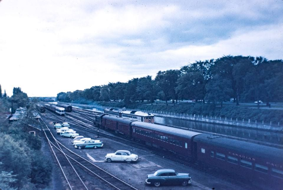 Self-propelled aluminum cars approach (leave?) Ottawa's Union Station through the rail yards on the east side of the Rideau Canal in the mid-1950s.  They're the cars behind the CP passenger train in the foreground.  The other side of the canal doesn't look much different today!  (CSTM Stowell Collection)