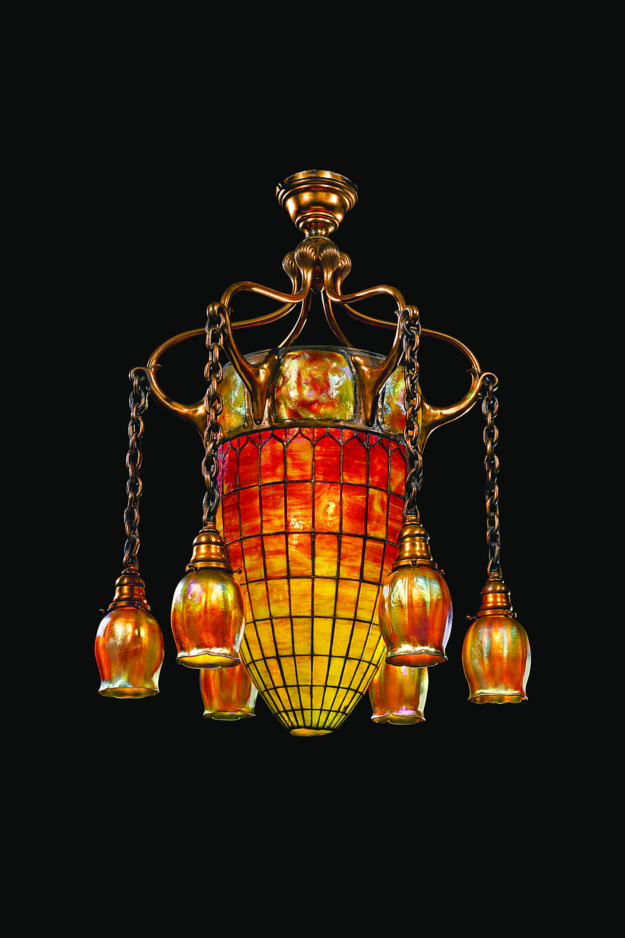 """A Tiffany Studios New York leaded glass and coppered bronze """"Geometric"""" chandelier with six golden """"Tulip"""" shades. The central shade is  mottled glass circa 1900. 