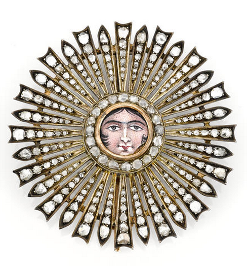 An enamel and diamond brooch, circa 1880 composed of an enamel portrait in a rose-cut diamond surround, backed by a starburst of additional rose-cut diamonds; mounted in silver-topped ten karat gold; diameter: 2 1/2in.