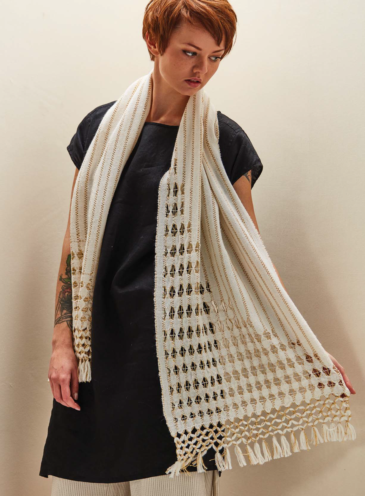 """Bring a little Gatsby-esque glamour with a show-stopping handwoven shawl. The hand-manipulated metallic lace """"bubbles"""" in this luxurious wrap were inspired by bubbles rising in a glass of champagne. Combining modified Brooks bouquet and Danish medallion techniques creates art-deco inspired panels of delicate lace in this rigid-heddle shawl. The knotted fringe finish is a nod to handwork found on shawls from the early twentieth century."""
