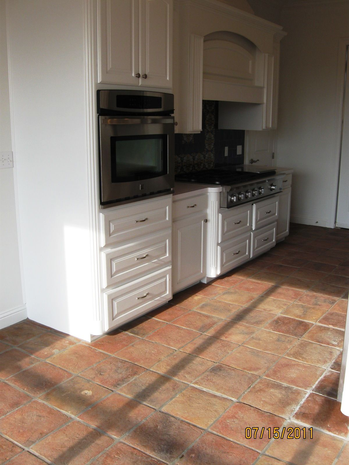 Antique terracotta saltillo tile really adds to the appeal of this antique terracotta saltillo tile really adds to the appeal of this white classic kitchen old world charm with antique saltillo terra cotta pinterest dailygadgetfo Image collections