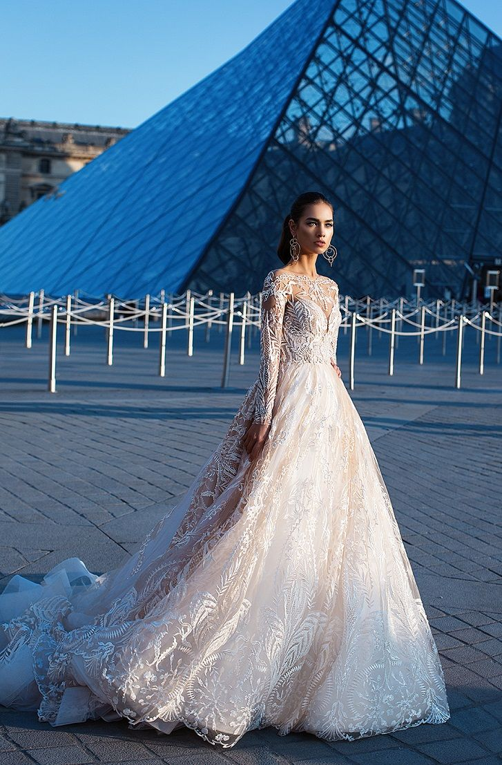 Long sleeves massive ornamental elements embroidered with beads and pearls. Multi layered lace skirt with nude color lining. A-silhouette dress with sleeves #weddingdress #wedding #weddinggown