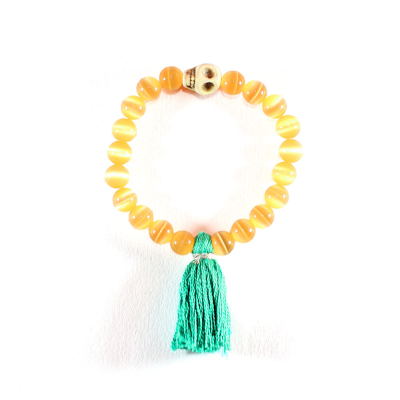 BRINGS HAPPINESS A stretch bracelet of Orange Synthetic Cat's Eye gemstones decorated with a ivory white skull bead and a emerald green tassel.