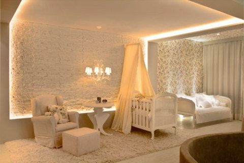 Em tons de bege e rosa, a arquiteta Renata Dutra criou a Suíte do bebê. A parede principal é revestida por uma placa cimentícia, de 30 x 60 cm, da Solarium. O berço de madeira maciça entalhada e pintada de branco. Um tecido floral reveste a parede e o teto. Acima do berço, um cortinado bege harmoniza com o enxoval.
