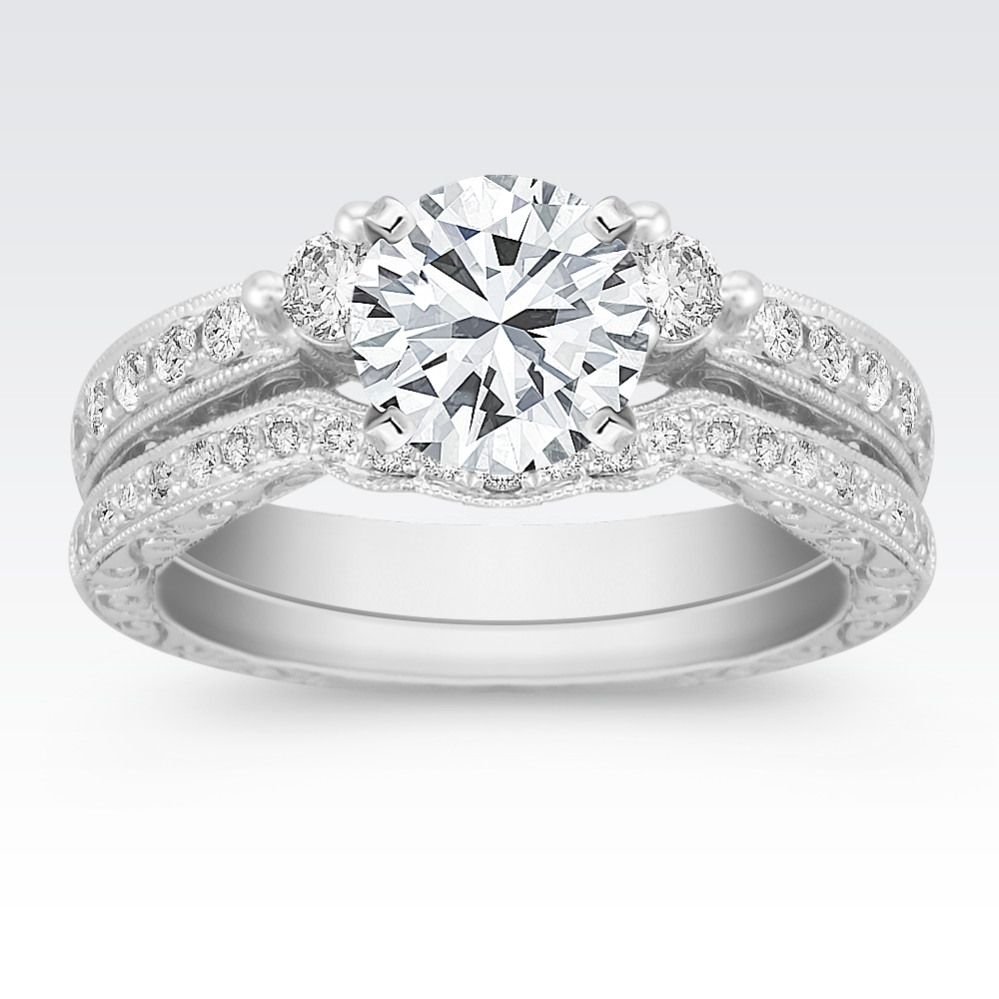 This vintage inspired wedding set crafted in quality 14 karat white gold features 35 round pavé-set diamonds, at approximately .61 total carat weight.  Each stone has been hand-selected for exceptional fire and brilliance.  Simply add the center stone of your choice to complete this beautiful set.