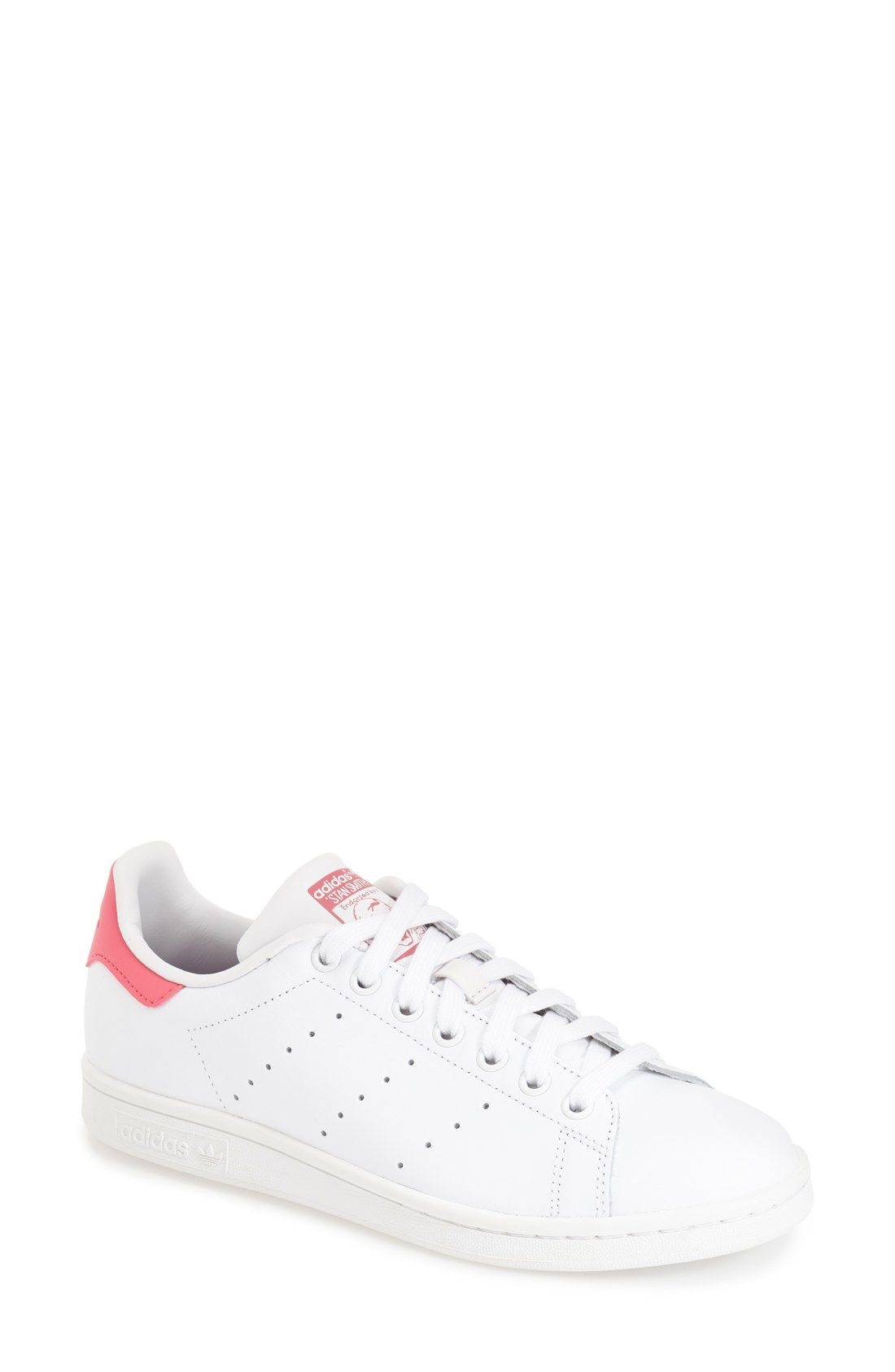 Adding a feminine touch to the classic Adidas Stan Smith sneaker by adding  pink details.