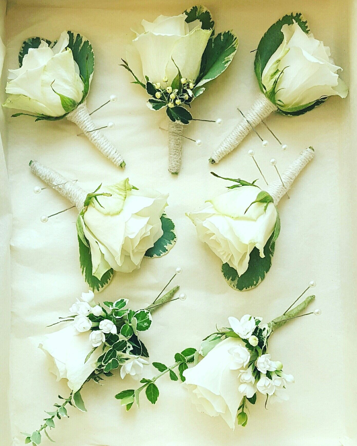 Classic White Rose Buttonholes with variegated foliage and twine