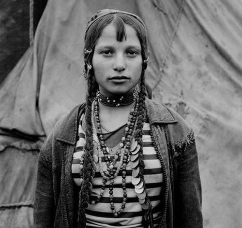 """Roma girl. Sintesti, Romania. 1990. The Romani ethnic group lives mostly in Europe, genetically traced from N.W. Indian Subcontinent ca. 1500 years ago. The English word """"Gypsy"""" from mid-16th C. 'gipcyan', a corruption of 'Egyptian' based on an idea that they came from Egypt. Photo by Jeremy Sutton Hibbert."""