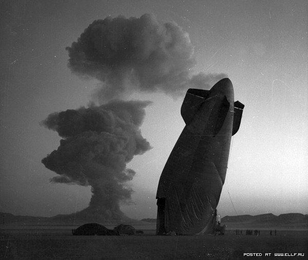 16. Хвостовая часть беспилотного дирижабля ВМС США. На заднем фоне — ядерный взрыв на полигоне в штате Невада, 7 августа 1957 года. Дирижабль летел в 8 километрах от места испытания, но рухнул от ударной волны. (Фото Nevada Site Office):