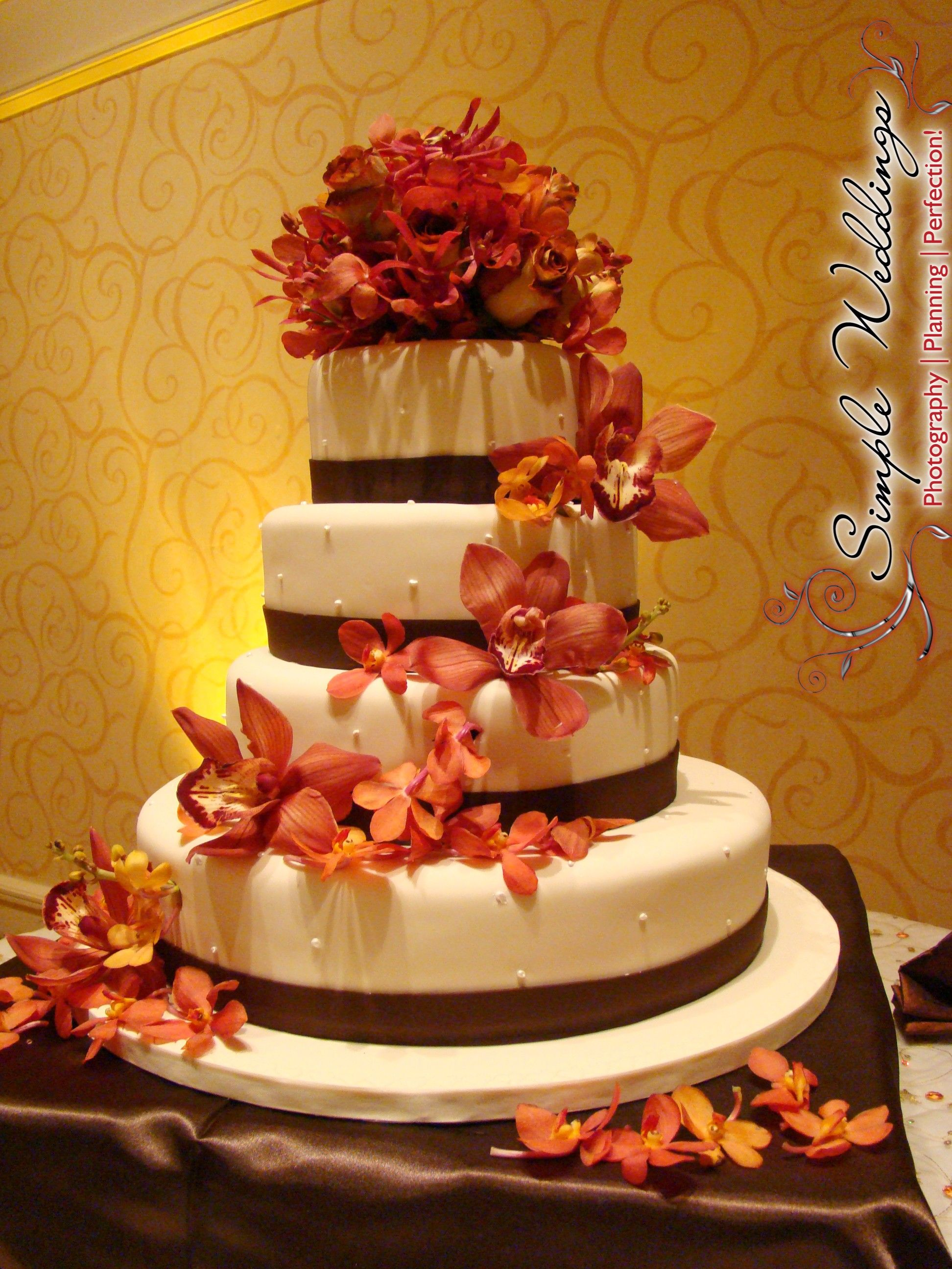 elegant cream and brown four-tier wedding cake with burnt orange