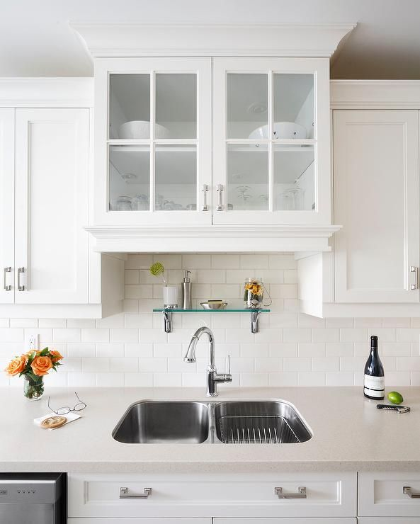 Glass doors & shelf above kitchen sink create a soft light feeling in this  small kitchen