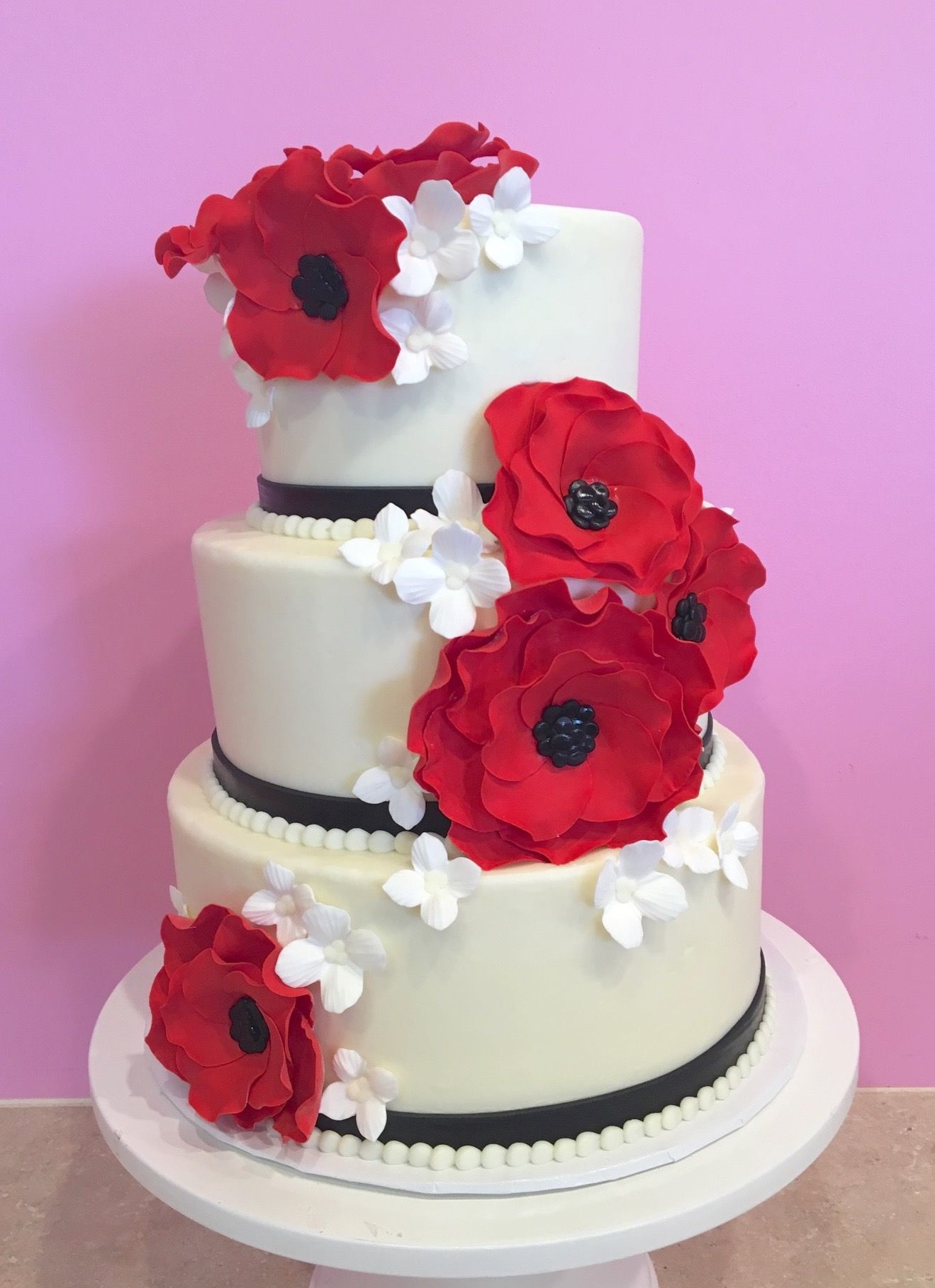 3 Tier Wedding Cake With Red Flowers And Tiny White Accent Flowers