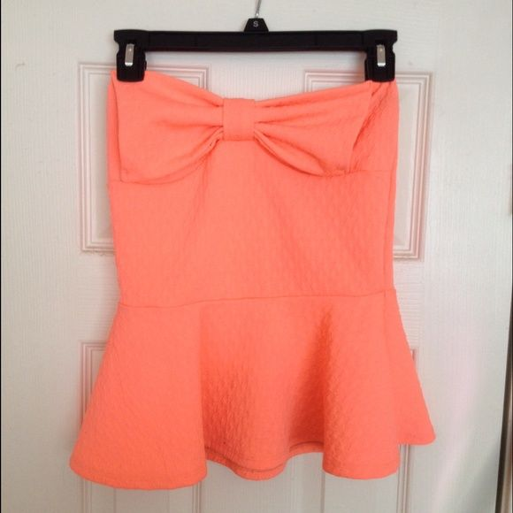 Neon coral strapless peplum top Worn 1x. No flaws. Very bright and pretty coral color! Perfect with a tan. Has beautiful bow detailing ! Fits like a small! Charlotte Russe Tops