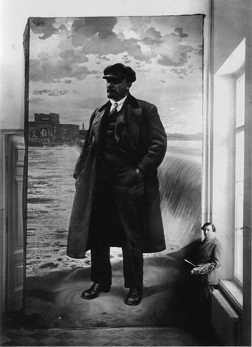 The artist Isaak Brodsky standing beside a portrait of Vladimir Lenin painted for the Conference Hall at Smolny, 1927.