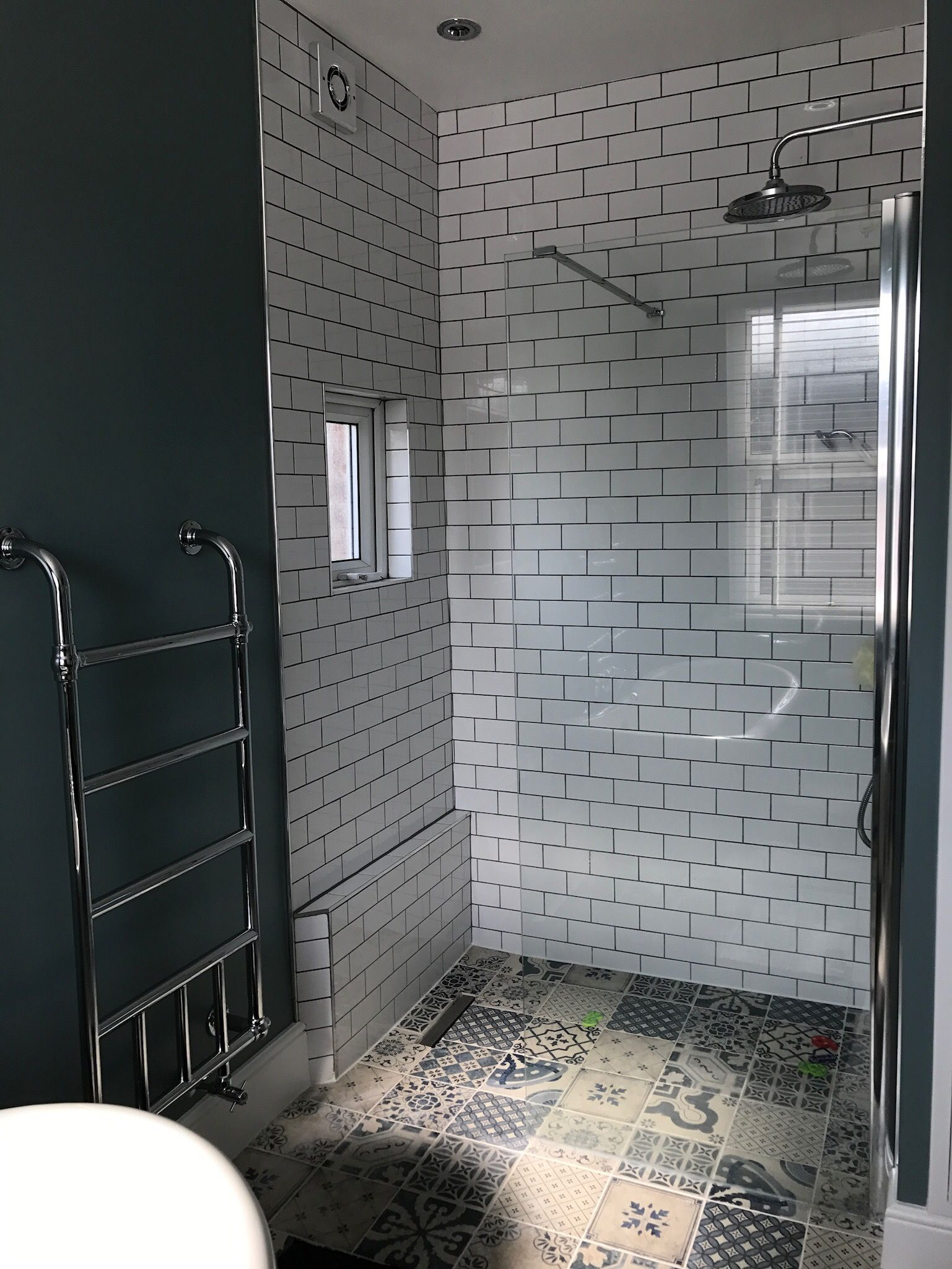 Bathroom. White brick tiles, grey grouting, oval room blue