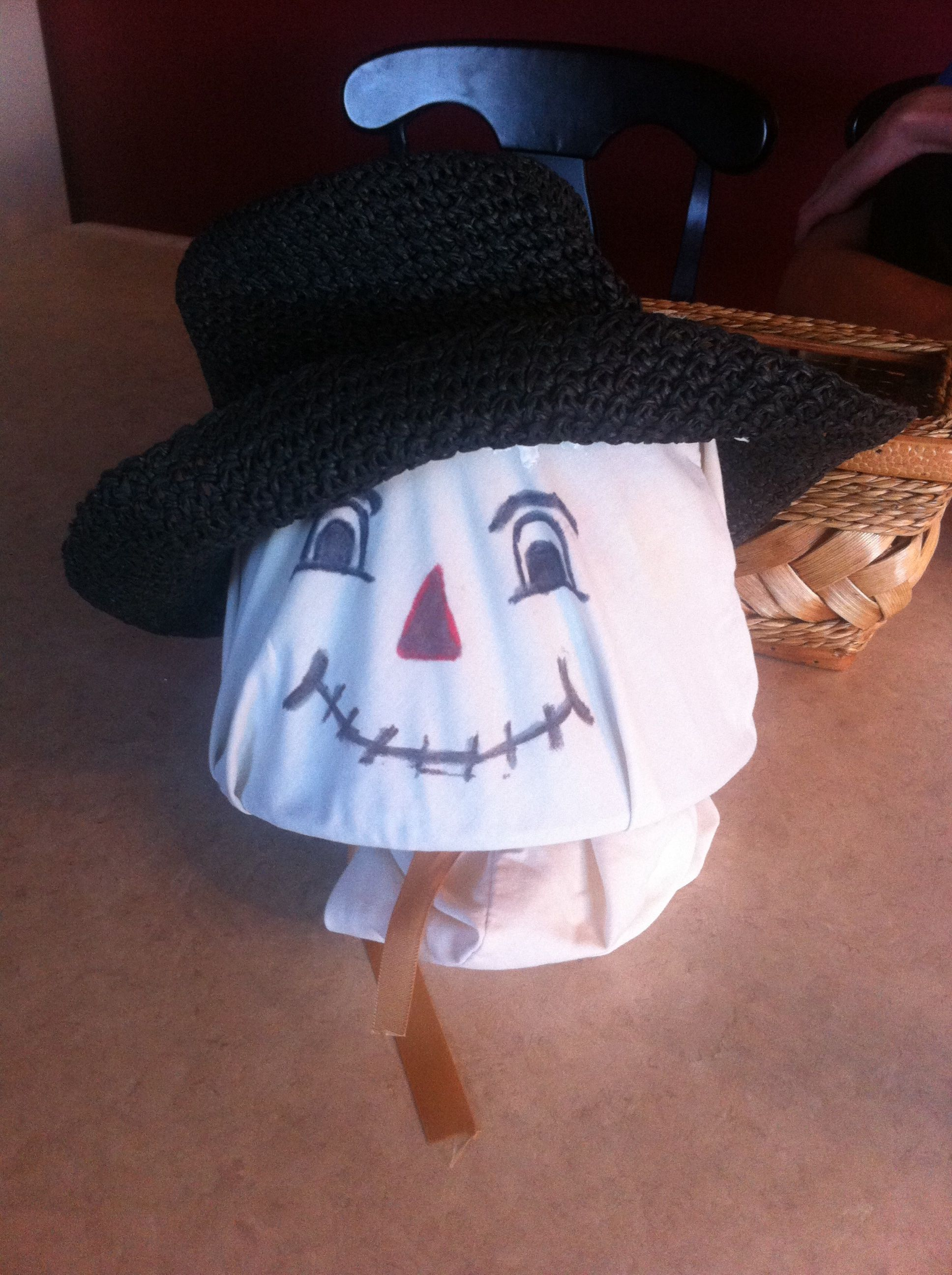 Turned an old plastic Easter bucket upside down, covered with a pillow case, add a face and hat and you have your scarecrow's head