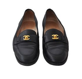 Black leather loafers feature overlapping leather straps that buckle with a gold-tone crossed Cs insignia accent. Sturdy rubber sole. Size 41