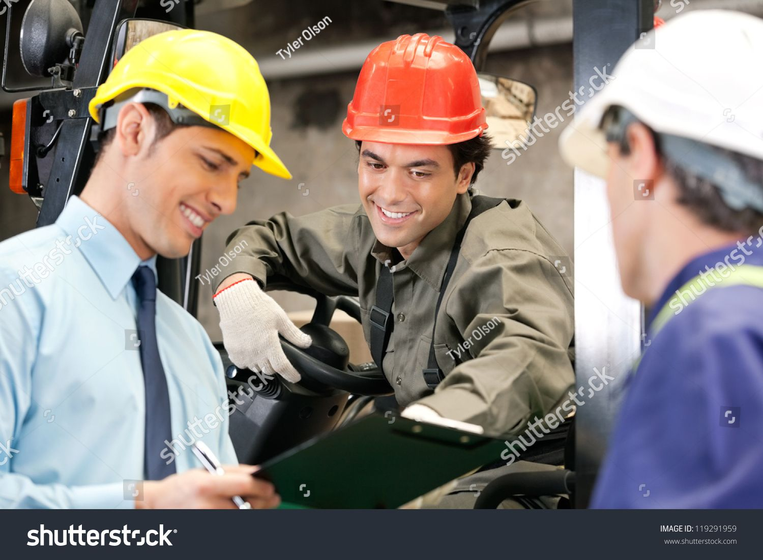 Happy young forklift driver with supervisor holding