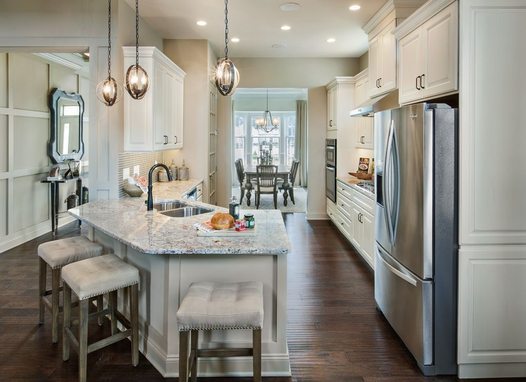Traditional Kitchen With Raised Panel Peninsula Pendant Light Hardwood Floors Complex Granite Counters Galley