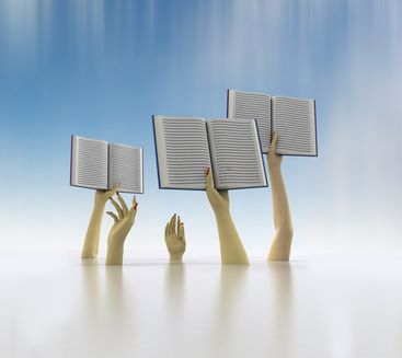 arms holding three books on blue blur background