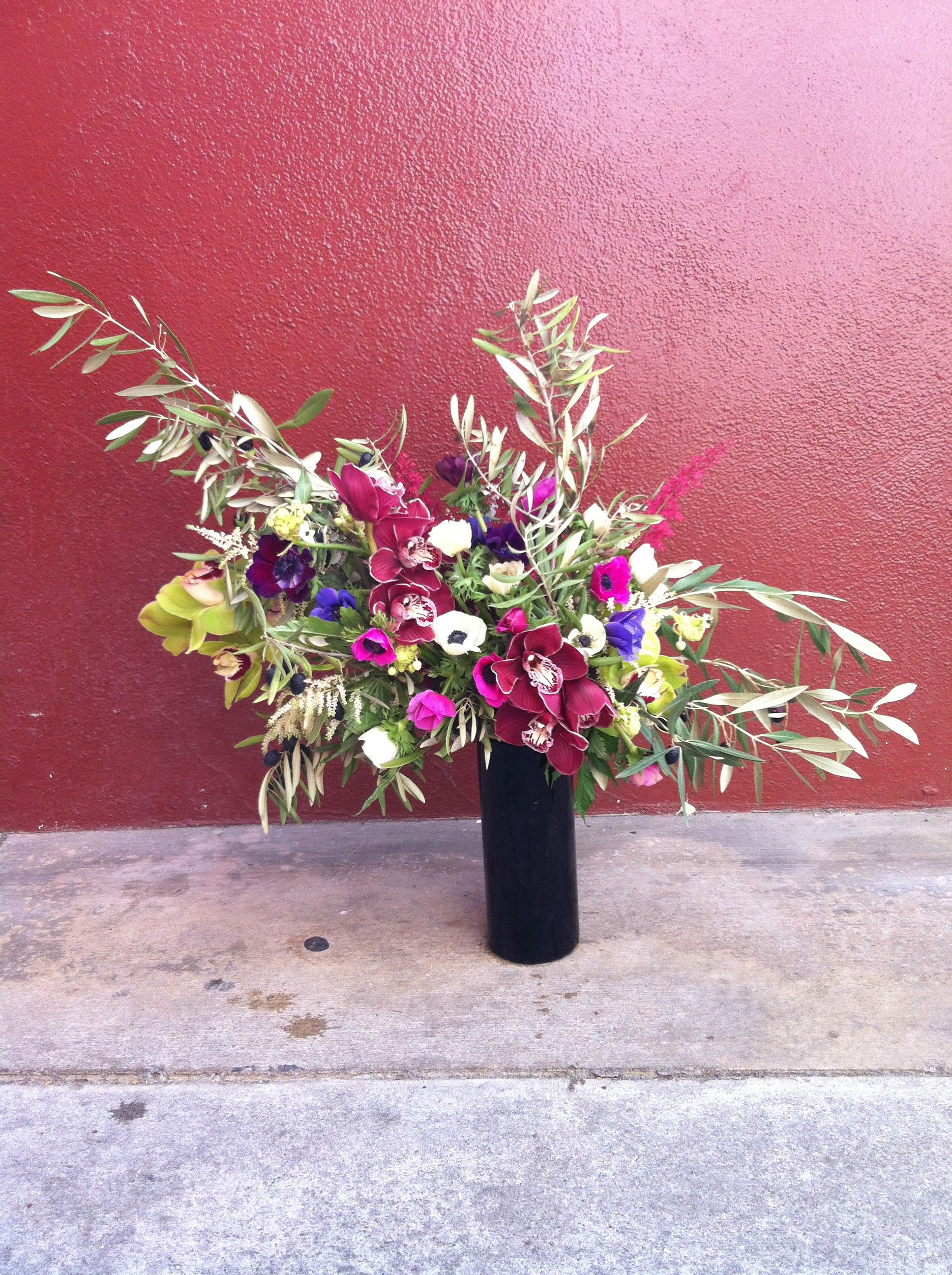 Arrangement By Botany Including Olive Branches Orchids Anemones Astilbe And Arabica In Black Glass Vase