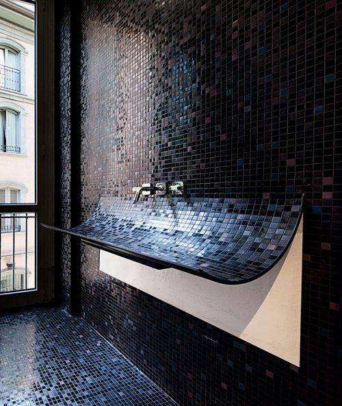 Unique Curved Bathroom Sink With Black Mosaic Tile Plus It Doubles As A Diaper Changing Station For Guests