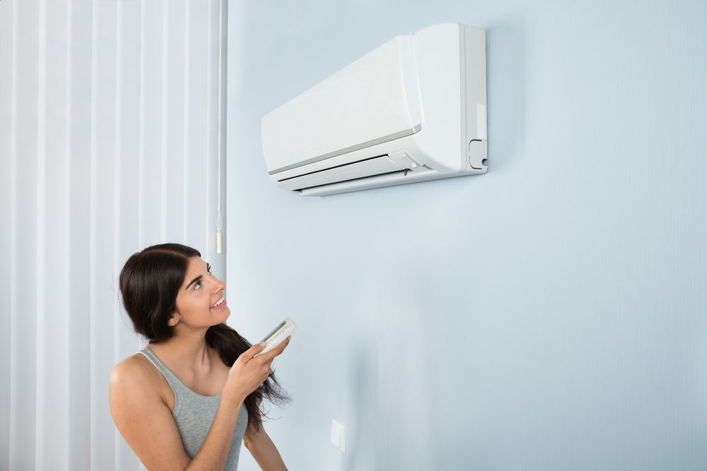 A Woman Turns On Her Wall Mounted Ac Unit In San Diego Split System Air Conditioner Air Conditioner Installation Air Conditioning System