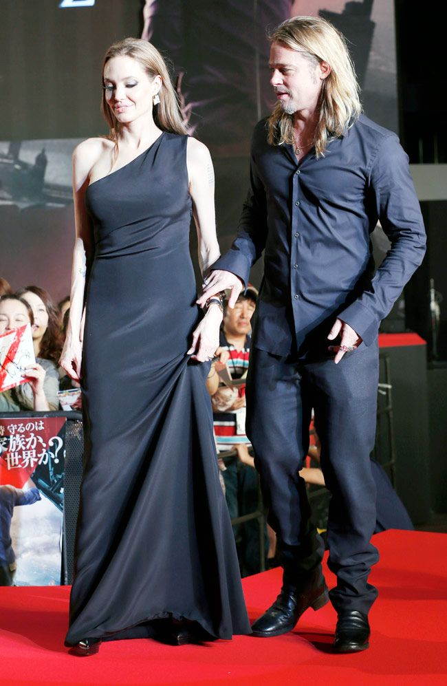 Angelina Jolie and Brad Pitt pose for the shutterbugs in style at the Japan premiere of World War Z. Jolie looked stunning in an one-shoulder black gown. #Hollywood #Fashion