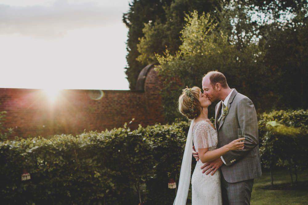 Image by Rebecca Goddard - Pronovias Embellished Wedding Dress & Jenny Packham Veil with Flower crown head piece, Peach Bridesmaids gowns, Grey Groomsmen suits & retro tassel lampshades decor.