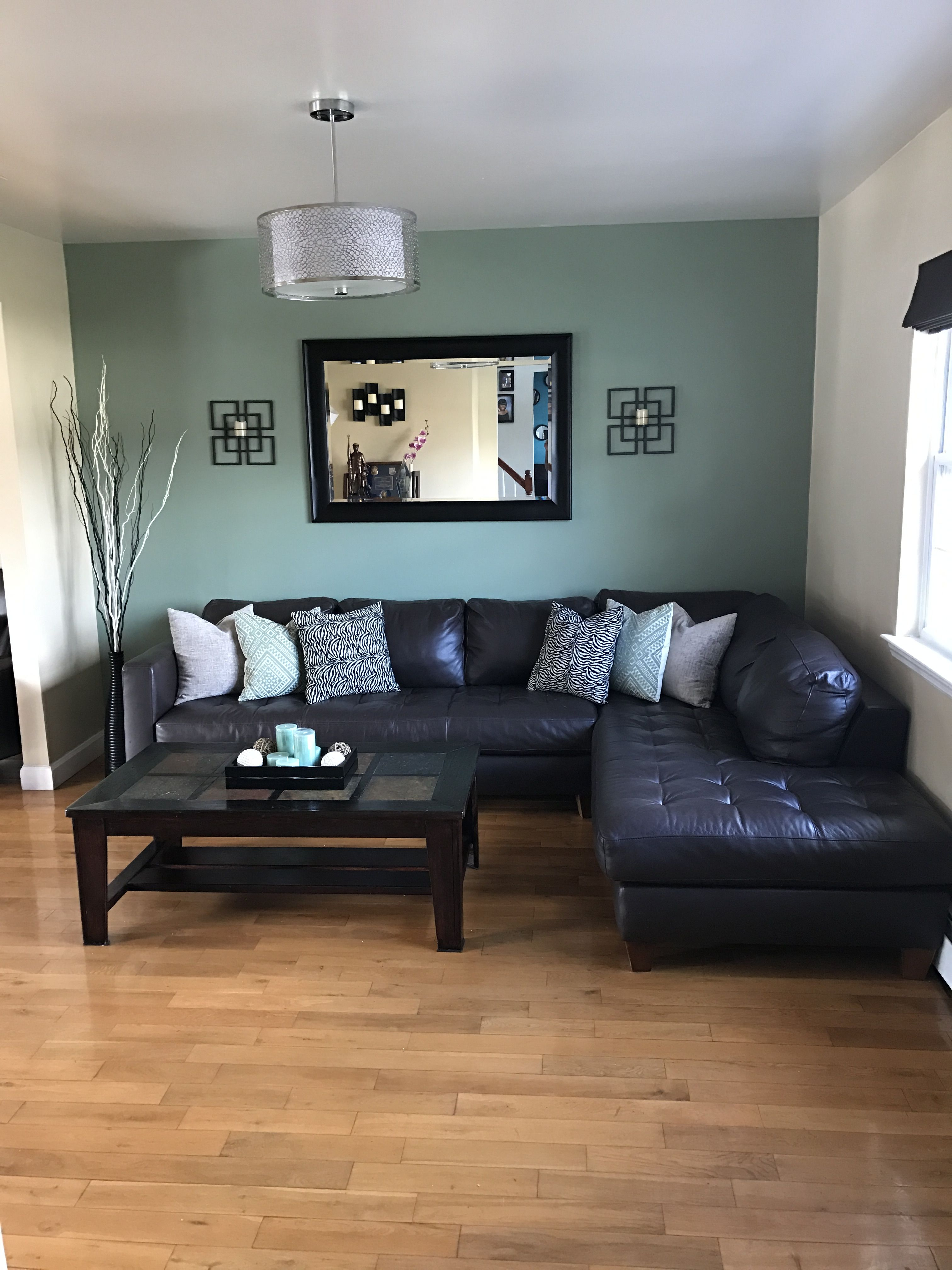 Dark brown sectional looks great with sage green accent wall